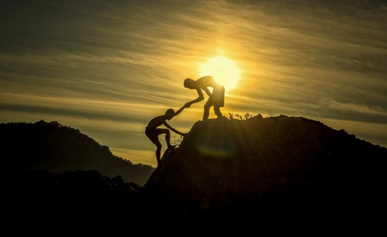 Boy helping another boy up a steep hill