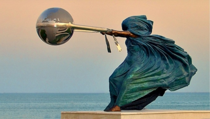 Statue of female figure in robes swinging earth globe with a piece of cloth