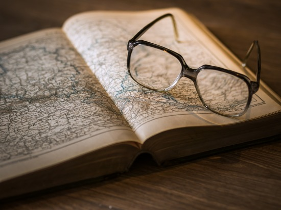 Eyeglasses on top of an open book of maps