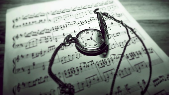 A pocket watch on lying on top of a music score