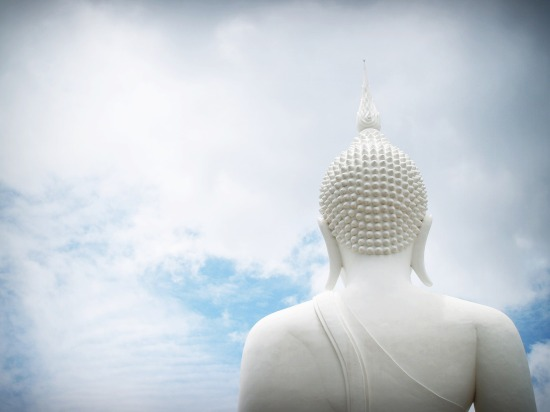 The back of the head of a white statue of Buddha against a partially cloudy sky