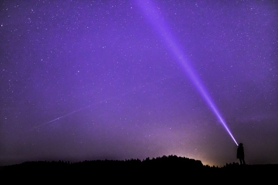 Silhouette of person pointing a flashlight up into a purple-tone night sky